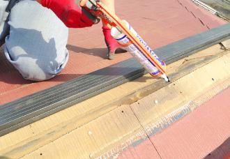 釘穴をふさぐためのシーリング補修の作業中