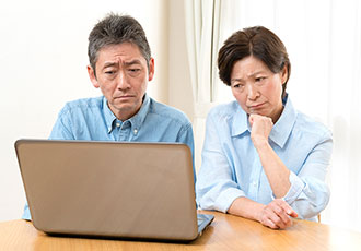 パソコンを見て悩む夫婦