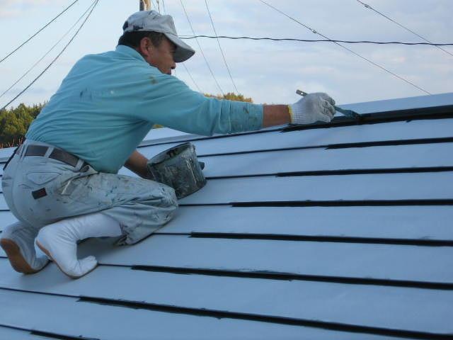福島市内にあるトタン鋼板の横葺き屋根の狭小部を刷毛で中塗りしています。
